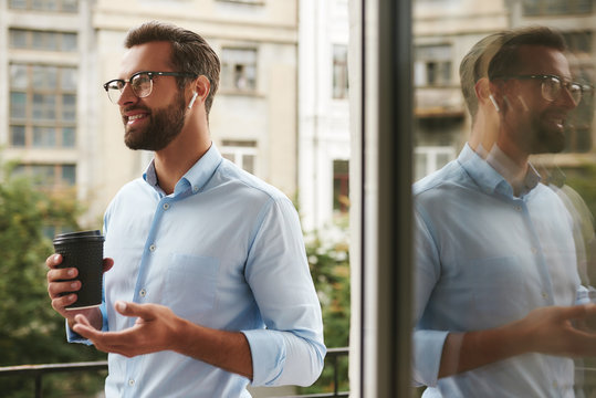 Glad to hear you Portrait of young and handsome bearded man in eyeglasses and headphones holding cup of coffee and talking with client while standing at the office balcony