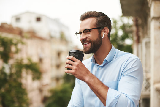 Positive news. Young and handsome bearded man in eyeglasses and headphones holding cup of coffee and talking with friend while standing at the office balcony
