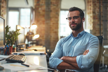 Young and successful. Portrait of handsome bearded man in eyeglasses and headphones keeping arms crossed and smiling while sitting in the modern office Wall mural