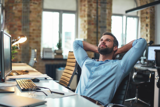 Enjoying break. Satisfied young bearded businessman leaning back with hands behind head and relaxing while sitting in the modern office