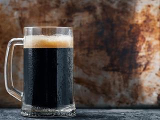 Dark beer mug on rustic dark copyspace background