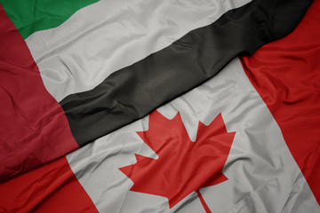waving colorful flag of canada and national flag of united arab emirates.