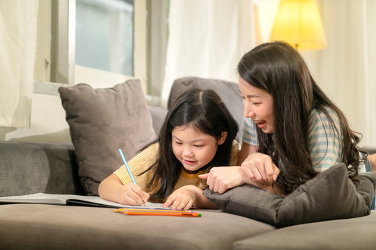 happiness asian family mom teach homework together with daughter on sofa relax and casual study home background