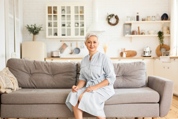 Indoor image of attractive elegant Caucasian retired woman with short gray hairdo wearing stylish blue dress sitting on sofa in relaxed pose, looking at camera with calm joyful smile. People and age