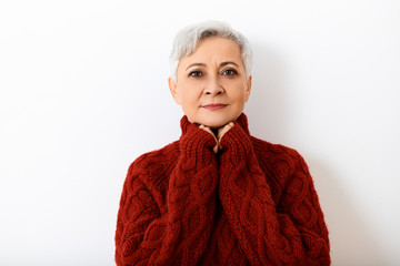 People, age, style, fashion and seasons concept. Picture of beautiful happy senior sixty year old woman with short pixie hairdo holding hands under her chin and smiling, dressed in knitted sweater