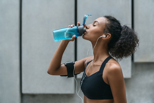 Fitness woman drinking water from a bottle after workout standing by a grey wall