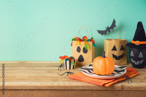 Halloween holiday table setting with glitter pumpkin, party gift paper bag decor and candy