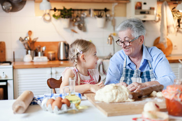 Senior woman and child make dough for bread together. Family is cooking in cozy kitchen at home. Grandmother is teaching little girl. Cute kid is helping to prepare meal for Thanksgiving Day dinner.
