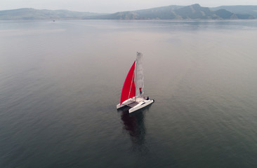 Aerial view shows a couple traveling on a sailing catamaran along the Yenisei River in Krasnoyarsk region
