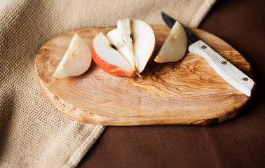 Fresh Forelle pear cut up with a paring knife on wooden cutting board