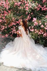 beautiful woman with dark hair in luxurious wedding dress posing near flowers