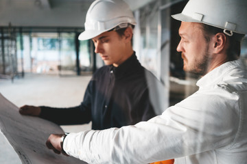 Industrial architect discussing build drawing with worker wearing safety hard hat. Two building engineers lookin at blueprint on construction site