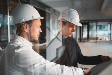 Building worker and architect discussing build drawing on construction site. Two industrial engineers wearing safety hard hat have meeting on commercial building structure