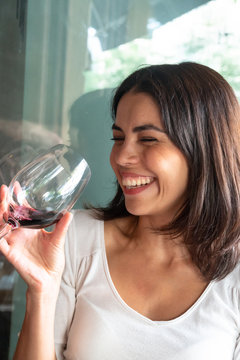 Laughing brunette young woman holding a glass of red wine