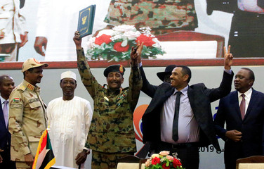 Sudan's Head of Transitional Military Council, Lieutenant General Abdel Fattah Al-Burhan, and Sudan's opposition alliance coalition's leader Ahmad al-Rabiah, celebrate the signing of the power sharing deal, in Khartoum