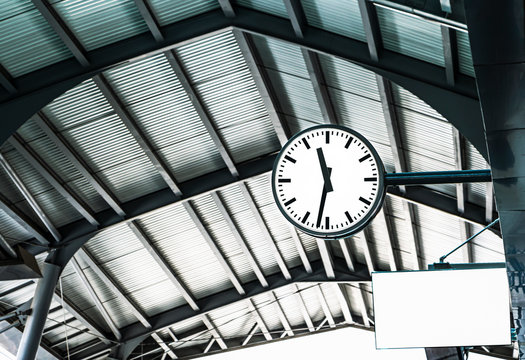 Large clock on the train station. Railway station clock hanging onto the roof.