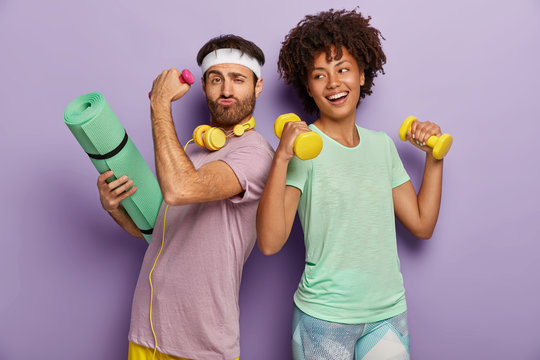 Glad multiethnic husband and wife attend sport center, exercise with dumbbells, hold fitness mat, stand back to each other, have funny happy looks, wear t shirts, isolated on purple background