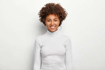 Photo of charismatic lovely woman with curly hair, has fun, toothy smile on face, satisfied after successful deal, looks at camera, wears white casual clothes, poses in studio. Happy emotions Fototapete