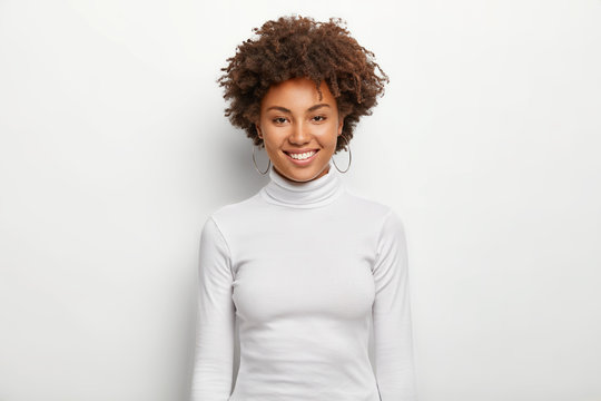 Photo of charismatic lovely woman with curly hair, has fun, toothy smile on face, satisfied after successful deal, looks at camera, wears white casual clothes, poses in studio. Happy emotions