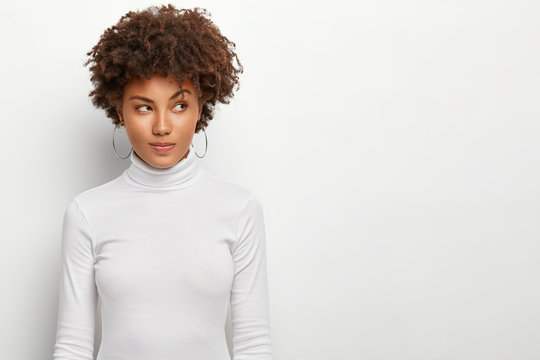 Serious woman contemplates about something, raises eyebrows, has pensive look, thinks about some question, concentrated aside, wears casual white sweater, copy space area on white background