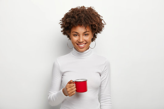 Beautiful satisfied dark skinned teenager holds red mug with hot beverage, smiles at camera, wears white jumper, enjoys drinking fresh coffee or tea, glad with first sip in morning. Drinking