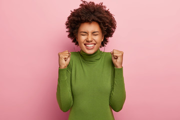 Photo of overjoyed Afro woman clenches fists with triumph, smiles broadly, rejoices new achievement, celebrates something, dressed in green turtleneck, wears big hoop earrings, keeps eyes shut