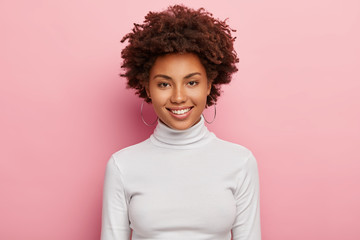 Gorgeous lovely woman has pleasant smile on face, healthy skin, Afro haircut, wears casual white turtleneck jumper, round earrings, looks happily directly at camera, has no make up, feels joyful