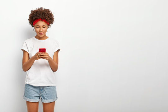 Indoor shot of attractive woman looks at screen of smart phone, sends messages to friend, checks email box in social networks, wears casual outfit, stands against white wall with blank space aside