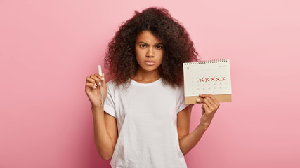 Menstrual cycle and feminine hygiene concept. Discontent dark haired African American woman holds...