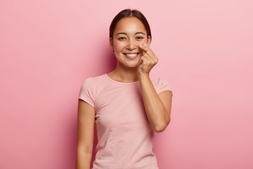 Lovely young female model touches genlty her rouge cheeks, shows healthy skin on face, has Asian appearance, smiles broadly, wears pink t shirt, poses indoor. People, ethnicity, beauty, skin care Wall mural
