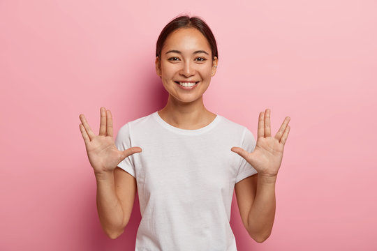 Young Asian female makes vulcan salute hand gesture, keeps arms raised and palms forward with extended thumbs, middle and ring fingers parted, greets you, says live long and prosper. Body language