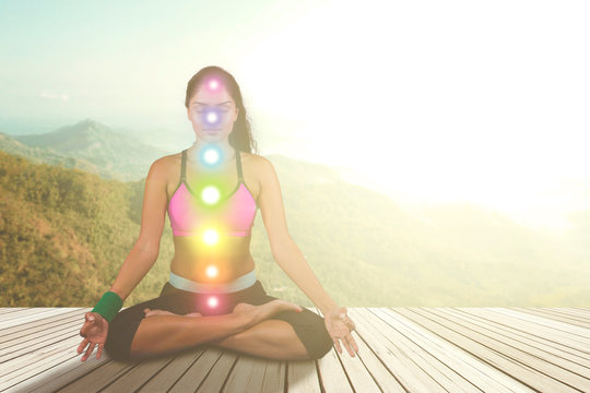 Woman meditating with colored chakra points