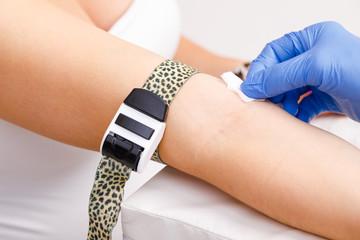 Nurse disinfecting skin preparing for taking blood sample from arm vein during venipuncture procedure