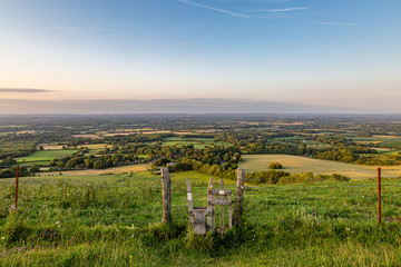 Looking out over the Sussex countryside from Ditchling Beacon, with a stile in a fence in the foreground Wall mural