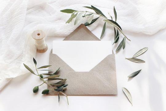 Feminine wedding stationery, desktop mock-up scene. Blank horizontal greeting card with craft envelope, silk ribbon and olive branches.White table background. Summer flat lay, top view.