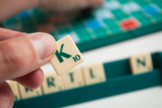Closeup of plastic letters K in hand on Scrabble board game
