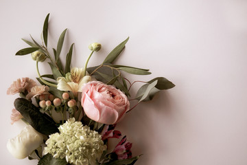 Horizontal image of fresh cut, pastel flowers and greenery on a white background with copy space