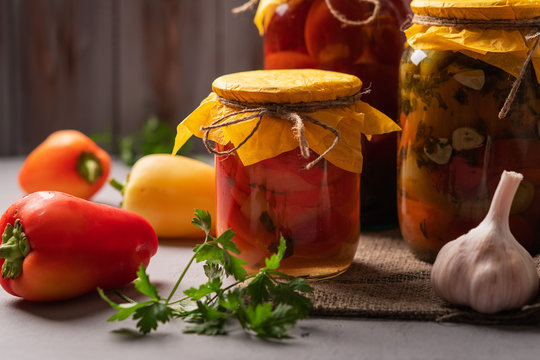 Homemade jars of pickled peppers and tomatoes on a rustic wooden background. Pickled and canned product. Next ingredients for cooking.