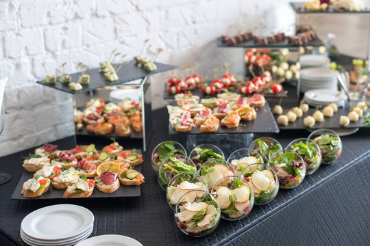 Beautifully decorated catering banquet table with different food snacks and appetizers.