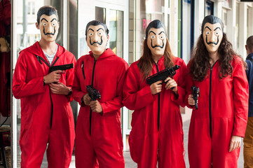 """group of fans of the serie tv """"La casa de papel (paper house)  on Netflix standing in the street with costume and Salvador Dali mask and false shot guns"""