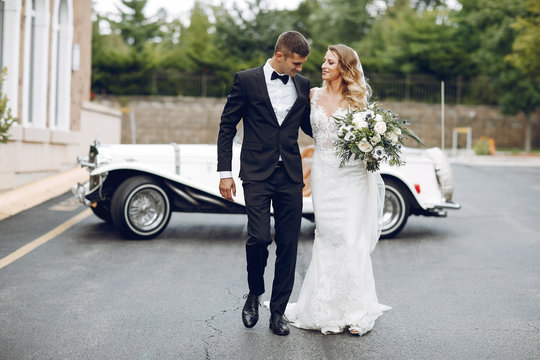 Beautiful bride in a long white dress. Handsome groom in a black suit. Couple near old car