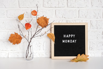 Happy Monday text on black letter board and bouquet of branches with yellow leaves on clothespins in vase on table Template for postcard, greeting card Concept Hello autumn Monday