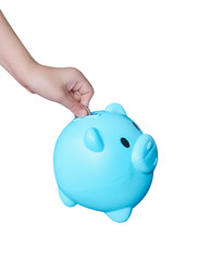 Asian little child hand putting coin in blue piggy bank or colorful empty money savings box isolated on white background with clipping path , top view