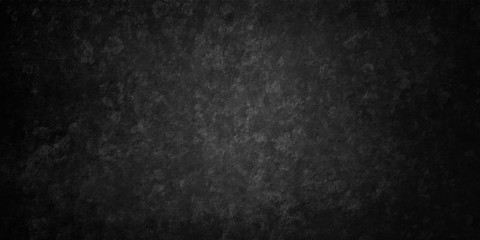 Black grunge texture on old background in distressed vintage design with a grungy rough surface in an elegant classy background with soft lit center and dark borders.