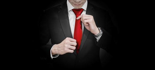 Businessman in black suit tying red necktie