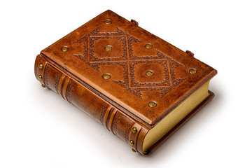 Bright brown aged leather book with decorative pattern on the front cover, gilded paper edges and two closure clasps.