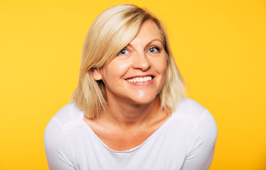 Happy smiling beautiful cute lovely blonde senior woman with beauty clean skin in casual wear isolated on yellow background. Healthcare and cosmetology concepts. Pensioner and mature people
