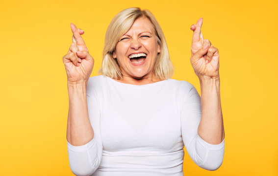 I very wish this stuff! Excited happy blonde senior woman is posing with crossing fingers isolated on yellow background