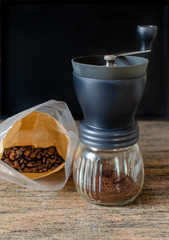 Modern hand coffee grinder and coffee beans on kitchen granite surface