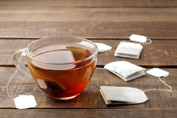 Tea bag in a glass cup on a brown wooden background. to make tea